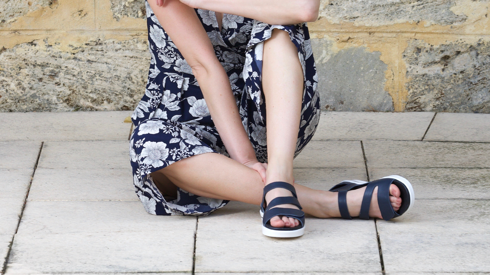 Woman sitting cross legged in navy Klouds Patience sandals